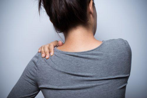 肩を揉む女性の後ろ姿