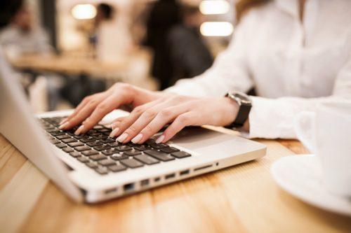 女性の手とパソコンのキーボード