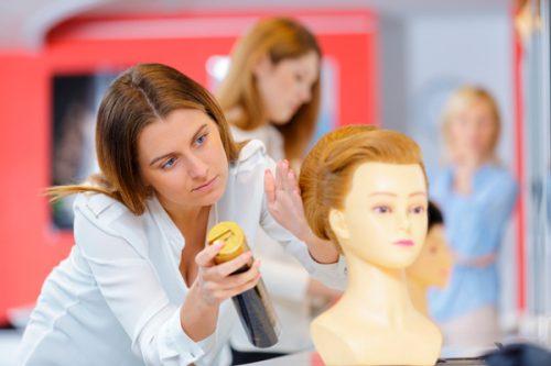 マネキンの髪をセットしている女性