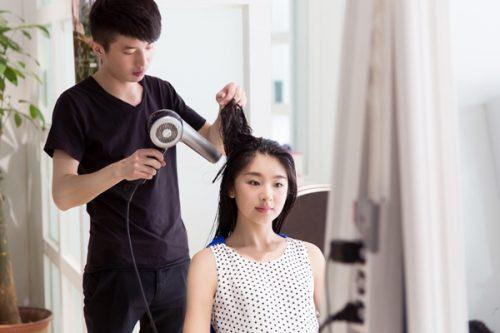 美容師さんに髪を乾かしてもらう女性