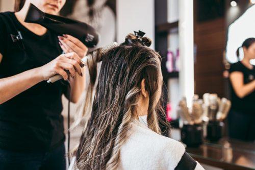 美容室で髪を巻いてもらっている女性