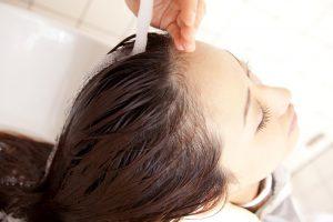 女子の髪を洗い流している