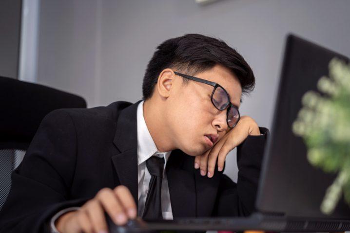 デスクで居眠りするサラリーマン