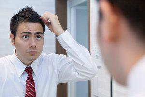 鏡の前で髪をセットする男性