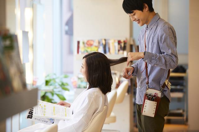 男性美容師が女性の髪を切っている